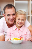 Happy little girl eating fruit with her father Royalty Free Stock Images
