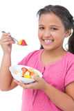 Happy little girl eating fruit salad Royalty Free Stock Image