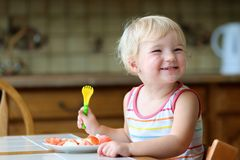 Happy little girl eating healthy salad indoors Royalty Free Stock Photos