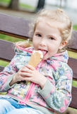 Happy little girl eating ice cream Stock Photos