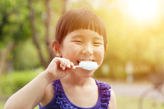 Happy little girl eating popsicle with sunset background Stock Images