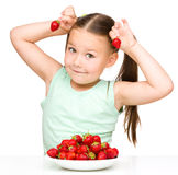 Happy little girl is eating strawberries Royalty Free Stock Images