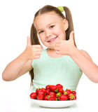 Happy little girl is eating strawberries Stock Photos