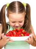 Happy little girl is eating strawberries Royalty Free Stock Photography