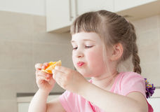 Happy little girl eating a tasty orange Royalty Free Stock Image