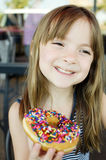 Happy little girl eating a tasty treat. Adorable little girl eating a chocolate sprinkle donut with a big smile on her face stock image