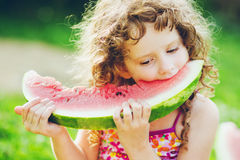 Happy little girl eating watermelon. Background toning to instag Stock Images