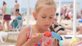 Happy little girl eating watermelon slices on the beach. Summer holiday picnic outdoors. Happy little girl eating watermelon slices on the beach. Summer holiday stock video footage