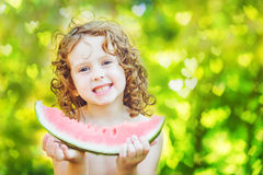 Happy little girl eating watermelon in summer park. Instagram fi Stock Images