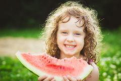 Happy little girl eating watermelon in summer park. Instagram fi Stock Photos