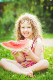 Happy little girl eating watermelon in summer park. Stock Photo