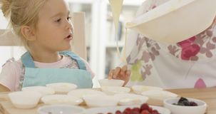 Happy little girl with empty muffin holders Stock Images