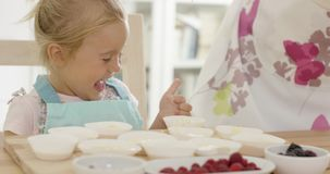Happy little girl with empty muffin holders stock video