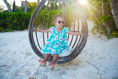 Happy little girl enjoy swing on white sandy Stock Image