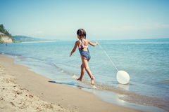 Happy little girl enjoying sunny day at the beach. With a ballon Royalty Free Stock Image