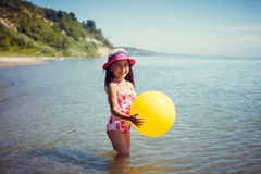 Happy little girl enjoying sunny day at the beach. Holds a big yellow ball Stock Photos