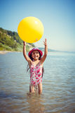 Happy little girl enjoying sunny day at the beach. Plays with a big yellow ball Royalty Free Stock Photo