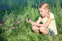 Happy Little Girl Exploring Nature With Magnifying Glass Stock Photos