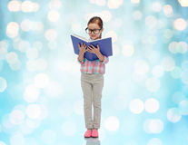 Happy little girl in eyeglasses reading book Royalty Free Stock Images