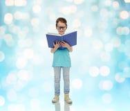 Happy little girl in eyeglasses reading book Stock Images