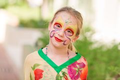 Happy little girl with face art paint in the park. Child`s birthday masquerade party have fun, laugh. Entertainment and holidays stock images
