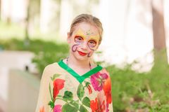 Happy little girl with face art paint in the park. Child`s birthday masquerade party have fun, laugh. Entertainment and holidays royalty free stock photo