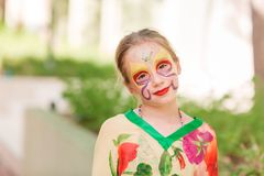 Happy little girl with face art paint in the park. Child`s birthday masquerade party have fun, laugh. Entertainment and holidays stock image