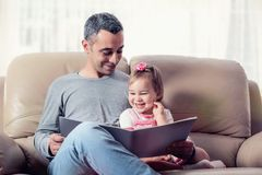 Happy Little Girl And Father Reading Book Together stock photo