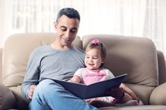 Happy Little Girl And Father Reading Book Together royalty free stock photo