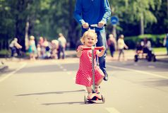 Happy little girl and father on scooters in the Royalty Free Stock Images