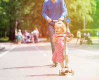 Happy little girl and father on scooters in the Royalty Free Stock Photo