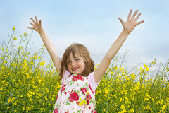 Happy little girl on a field Royalty Free Stock Image