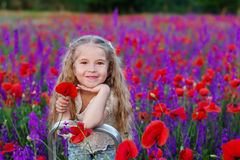 Happy little girl in a field of poppies Stock Photos