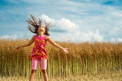 Happy little girl in a field of ripe rapeseed royalty free stock photography