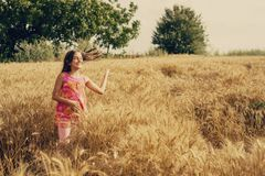 Happy little girl in a field of ripe rapeseed royalty free stock photo
