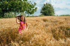 Happy little girl in a field of ripe rapeseed stock photo