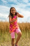 Happy little girl in a field of ripe rapeseed - vertical orientation royalty free stock images