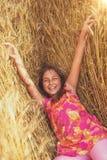 Happy little girl in a field of ripe wheat stock photo
