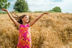 Happy little girl in a field of ripe wheat stock photos