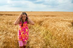 Happy little girl in a field of ripe wheat royalty free stock photography