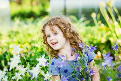 Happy little girl in a field with a spring wildflowers. Royalty Free Stock Images