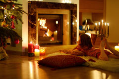 Happy little girl by a fireplace on Christmas Stock Image