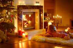 Happy little girl by a fireplace on Christmas Stock Photography