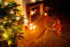Happy little girl by a fireplace on Christmas Stock Photos