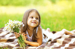 Happy little girl and flowers on the meadow in summer sunny day Stock Photo