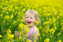 Happy little girl with flowers. Very happy little girl in the flower field. Field of Barbarea vulgaris. True happiness Royalty Free Stock Photography