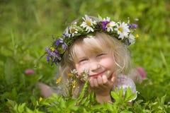 Happy little girl in flowers wreath royalty free stock photo