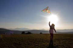 Happy little girl flying a kite on a hill of mountain at sunset royalty free stock photography