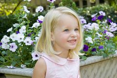 Happy little girl in front of pot of pansies. Little girl in front of flowers stock photos