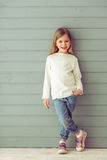 Happy little girl. Full length portrait of pretty little girl in casual clothes looking at camera and smiling, standing against gray background stock photography